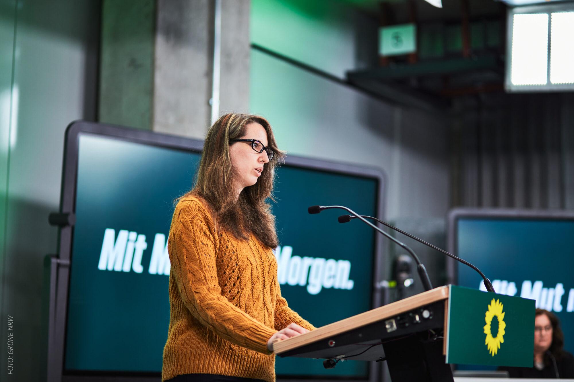 Sabine Grützmacher am Rednerpult der Landesdelegiertenkonferenz im APril 2021 in Düsseldorf - Gelber Pullover, im Hintergrund ein blaugrüner Groß-Monitor mit der weißen Aufschrift 'Mit Mut nach Morgen'