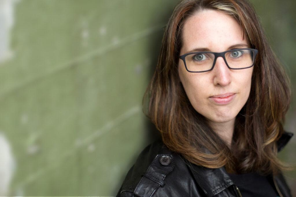 Sabine Grützmacher, nur der Oberkörper sichtbar, lehnt mit Rücken an einer grünen Mauer, schaut Richtung Betrachter:in, sie hat mittellanges, glattes, dunkelblondes Haar, die Stirn frei, trägt eine schwarze Brille, schwarze Lederjacke, die Lippen sind geschlossen
