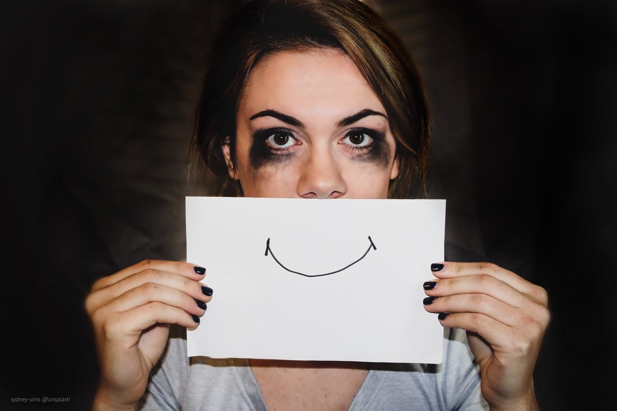 frau mit verweinten Augen hält weißes Blatt vor den Mund - auf dem Blatt ein lächelnder Mund