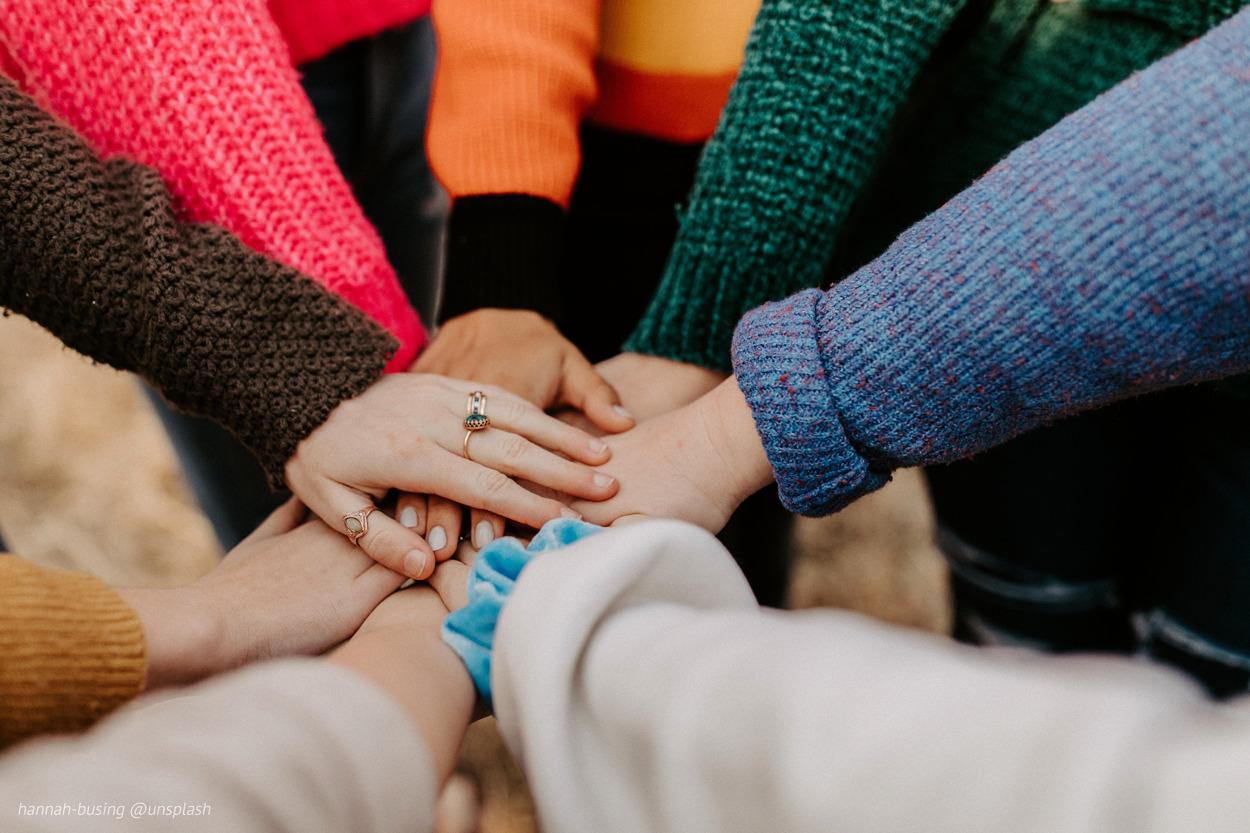 Eine Gruppe Menschen legt die Hände aufeinander, bunte Ärmel von Pullovern und Jacken in allen Farben - nur gemeinsam sind wir stark!