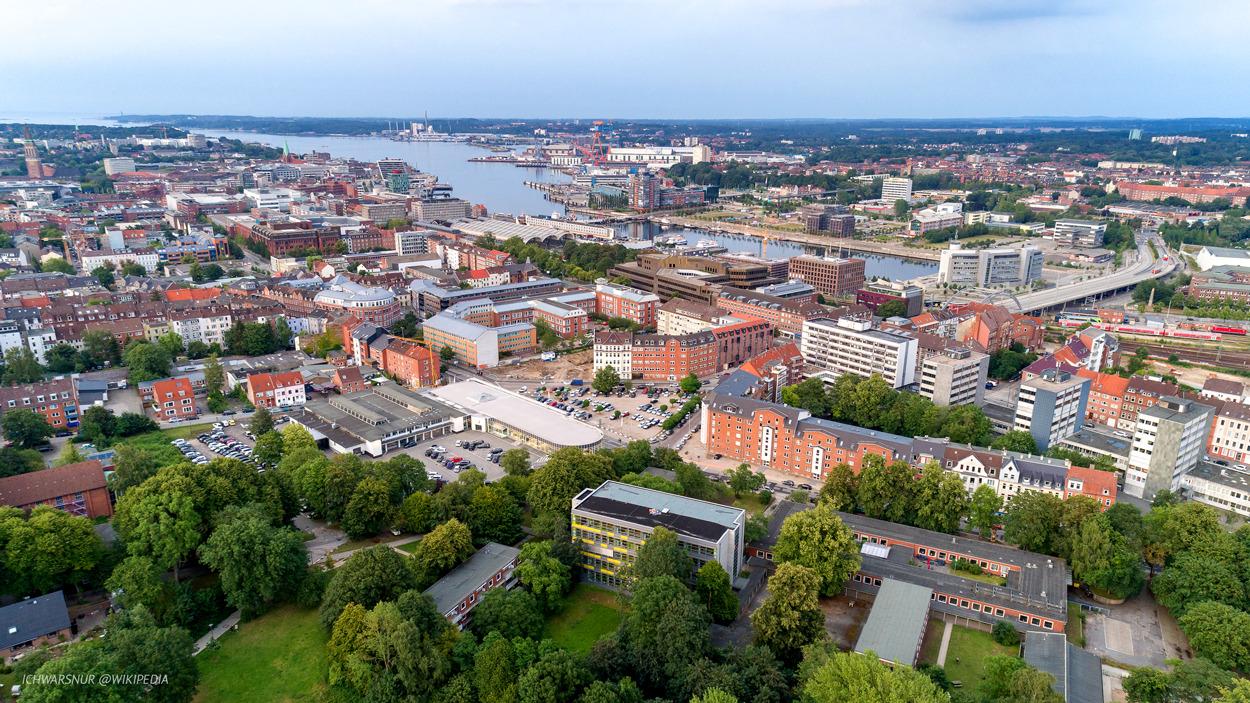 Luftaufnahme der Kieler Förde, unten links grün, die Moorteichwiese, darüber die Innenstadt und der Hafen. Am Horizont blau - die Ostsee.