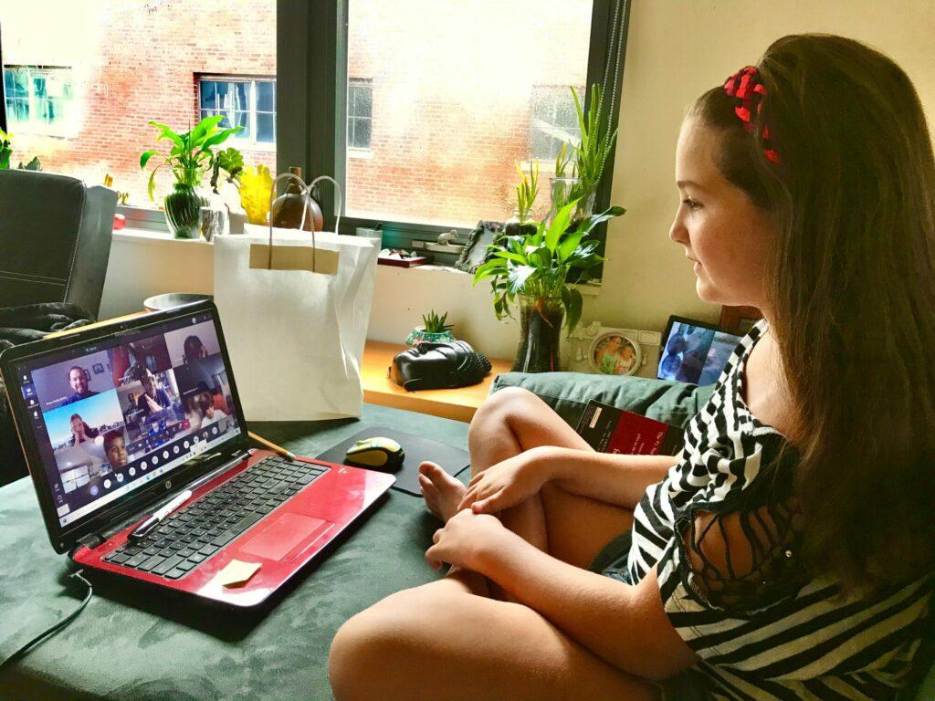 Mädchen sitzt im Wohnzimmer im Schneidersitz auf Sofa - auf dem Laptop-Bildschirm vor ihr ihre Klasse mit Lehrer in einem Online-Chat