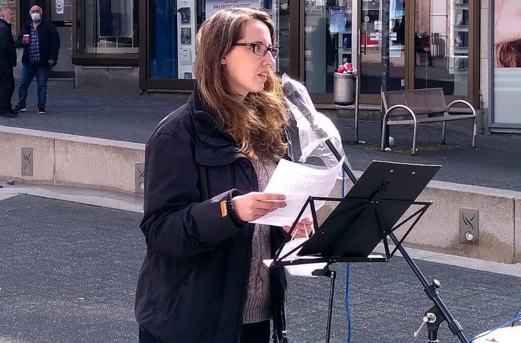 Sabine Grützmache steht auf der Straße in der Gummersbacher Fußgängerzone am Mikro und spricht zum Tag der Arbeit. Im Hintergrund Ladengeschäfte, Menschen, die sich unterhalten.